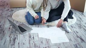 Couples heureux discutant le nouvel appartement de projet intérieur pendant le déplacement utilisant l'ordinateur portable dessin banque de vidéos