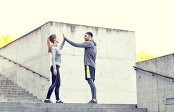 Couples heureux donnant la haute cinq dehors Photos stock