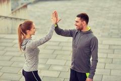 Couples heureux donnant la haute cinq dehors Images stock
