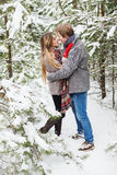 Couples heureux embrassant dans la forêt parmi des sapins dans la neige Images libres de droits