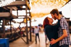 Couples heureux embrassant et embrassant le soir sur les guirlandes légères Photographie stock libre de droits