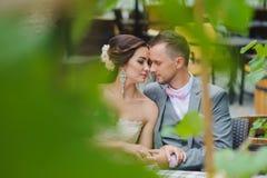 Couples heureux embrassant tout en se reposant en café de rue Image stock