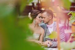 Couples heureux embrassant tout en se reposant en café de rue Photo libre de droits