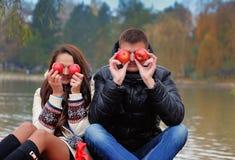 Couples heureux en Autumn Garden Avoir l'amusement sur l'herbe et consommation Image stock