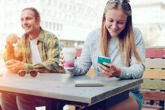 Couples heureux en café de rue ensemble, femme de sourire à l'aide du téléphone portable, dehors Photographie stock