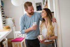 Couples heureux en café potable de matin d'amour à la maison Images libres de droits