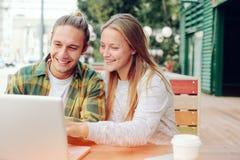 Couples heureux en café regardant l'ordinateur portable et discutant des plans Images stock