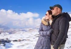 Couples heureux en montagnes de chute de neige Photos stock