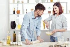 Couples heureux en pâte de malaxage d'amour dans la cuisine Photos libres de droits