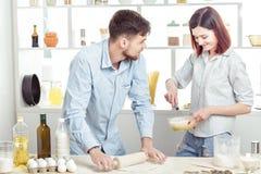 Couples heureux en pâte de malaxage d'amour dans la cuisine Image libre de droits