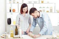 Couples heureux en pâte de malaxage d'amour dans la cuisine Images stock