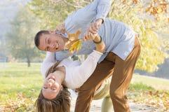 Couples heureux en parc ayant l'amusement dans le parc Photos stock