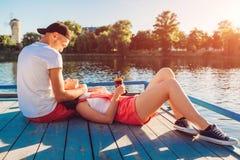 Couples heureux en refroidissement d'amour et café potable par la rivière au coucher du soleil Photos libres de droits