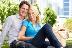 Couples heureux en stationnement de ville avec le pique-nique Image stock