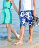 Couples heureux en vacances marchant tenant des mains sur le bord de la mer Photographie stock