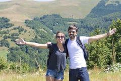 Couples heureux en voyage de hausse entourés par des montagnes Images libres de droits
