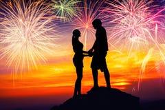 Couples heureux ensemble sur la roche et observer les feux d'artifice Images libres de droits