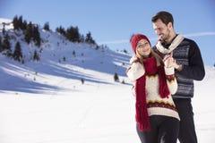 Couples heureux espiègles ensemble pendant des vacances de vacances d'hiver dehors en parc de neige Photographie stock