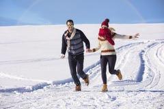 Couples heureux espiègles ensemble pendant des vacances de vacances d'hiver dehors en parc de neige Photo stock