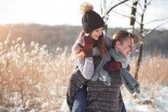 Couples heureux espiègles ensemble pendant des vacances de vacances d'hiver dehors en parc de neige Photographie stock libre de droits