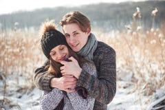 Couples heureux espiègles ensemble pendant des vacances de vacances d'hiver dehors en parc de neige Images stock