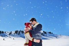 Couples heureux espiègles ensemble pendant des vacances de vacances d'hiver dehors en parc de neige Image libre de droits