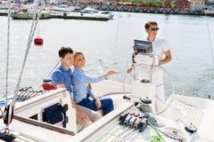 Couples heureux et beaux ayant un repos sur le yacht et observant c Images libres de droits