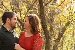 Couples heureux et jeunes dans la surface boisée de chute Photographie stock libre de droits