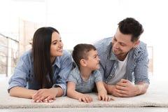 Couples heureux et leur fils se trouvant sur le tapis ? la maison images stock