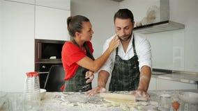 Couples heureux faisant cuire ensemble dans la cuisine Ils ont beaucoup de pâte de malaxage d'amusement et rire entre eux banque de vidéos