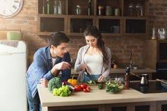 Couples heureux faisant cuire la nourriture saine ensemble Photos libres de droits