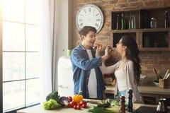 Couples heureux faisant cuire la nourriture saine ensemble Photographie stock libre de droits