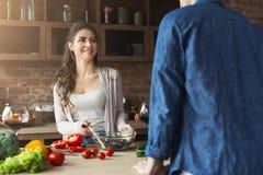 Couples heureux faisant cuire la nourriture saine ensemble Image libre de droits