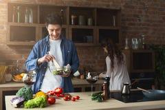Couples heureux faisant cuire la nourriture saine ensemble Photo stock
