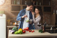 Couples heureux faisant cuire la nourriture saine ensemble Image stock