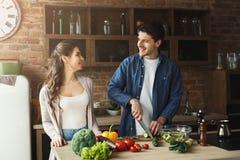 Couples heureux faisant cuire la nourriture saine ensemble Photographie stock