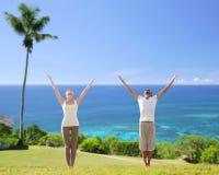 Couples heureux faisant des exercices de yoga sur la plage Photographie stock libre de droits