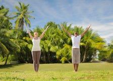 Couples heureux faisant des exercices de yoga sur la plage Image stock