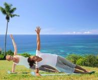Couples heureux faisant des exercices de yoga sur la plage Photos libres de droits