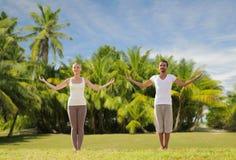 Couples heureux faisant des exercices de yoga sur la plage Photographie stock