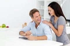 Couples heureux faisant des mots croisé cachés ensemble Images stock