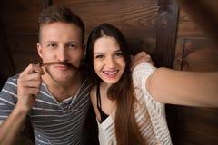 Couples heureux faisant des selfies d'isolement sur le fond en bois Images libres de droits