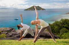 Couples heureux faisant le yoga dehors Image stock