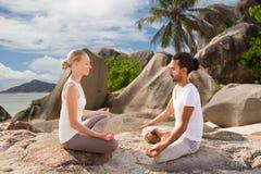Couples heureux faisant le yoga et méditant dehors Photos stock
