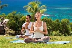 Couples heureux faisant le yoga et méditant dehors Image libre de droits
