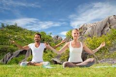 Couples heureux faisant le yoga et méditant dehors Image stock