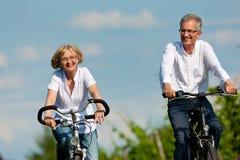 Couples heureux faisant un cycle à l'extérieur en été Photographie stock libre de droits