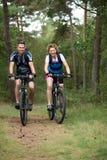 Couples heureux faisant un cycle en nature Images libres de droits