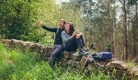 Couples heureux faisant une pause tout en faisant le trekking photos stock