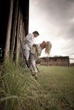 Couples heureux flirtant par espièglerie contre le mur de grange Image libre de droits